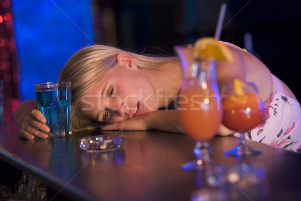 Stock photo: Drunk young woman resting head on bar counter