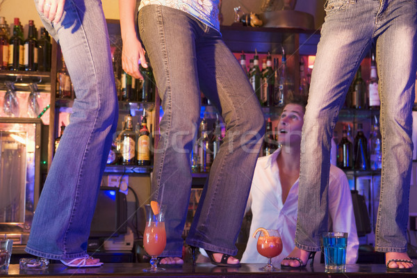 Barman gaping at three young women dancing on bar counter  Stock photo © monkey_business