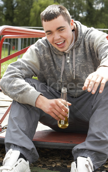 Young Man Sitting In Playground Drinking Beer Stock photo © monkey_business