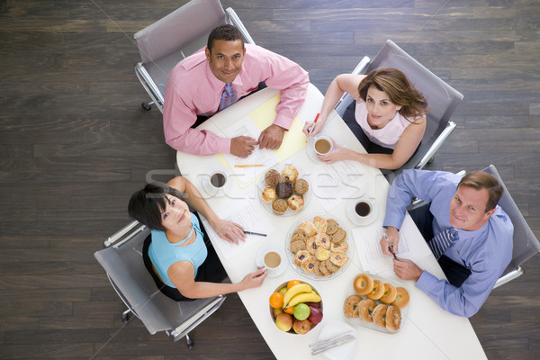 Four businesspeople at boardroom table with breakfast smiling Stock photo © monkey_business