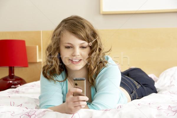 Teenage Girl In Bedroom With Mobile Phone Stock photo © monkey_business