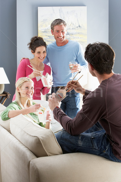 Stock photo: Group Of  Friends Enjoying Chinese Takeaway Meal At Home