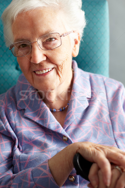Senior Woman Relaxing In Chair Holding Walking Stick Stock photo © monkey_business