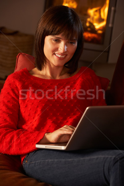 Middle Aged Woman Using Laptop Computer By Cosy Log Fire Stock photo © monkey_business