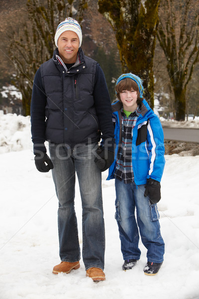 Father And Son Walking Along Snowy Street In Ski Resort Stock photo © monkey_business