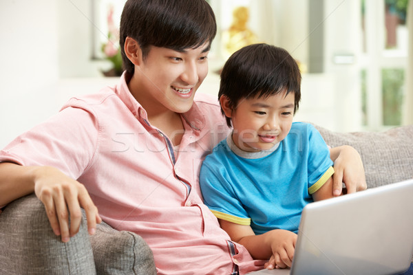 Stock photo: Chinese Father And Son Using Laptop Whilst Relaxing On Sofa At H