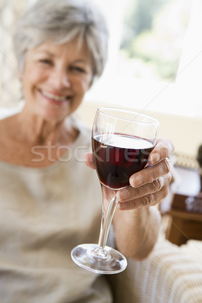 Woman in living room with glass of wine smiling Stock photo © monkey_business