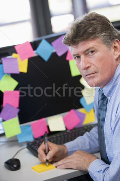 Businessman in office at monitor with notes on it writing Stock photo © monkey_business