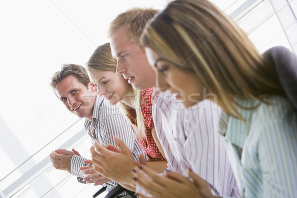 Four businesspeople applauding indoors smiling Stock photo © monkey_business