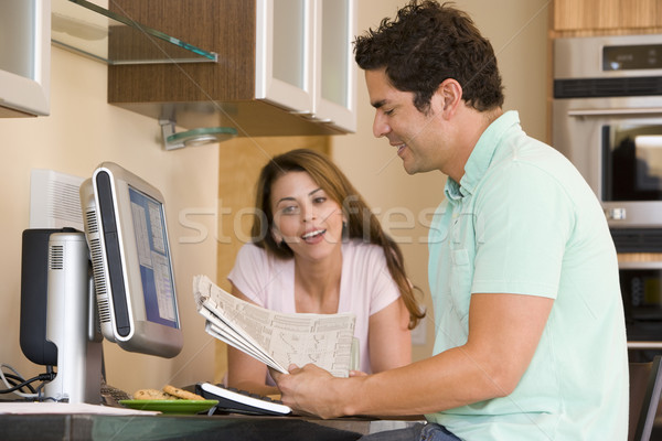Couple in kitchen with computer and newspaper smiling Stock photo © monkey_business