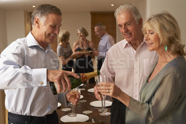 Stock photo: Man Serving Champagne To His Guests At A Dinner Party