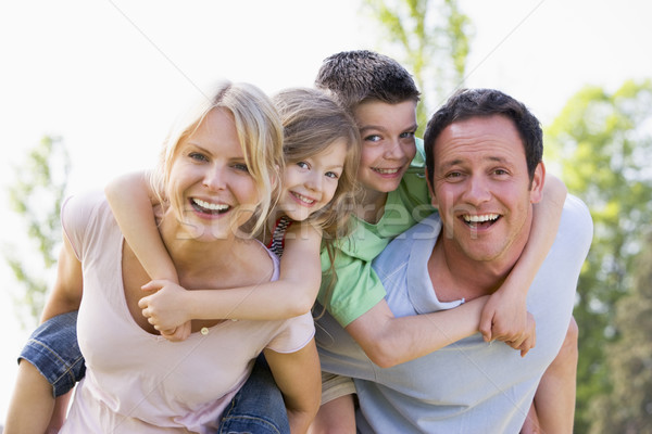 Couple giving two young children piggyback rides smiling Stock photo © monkey_business