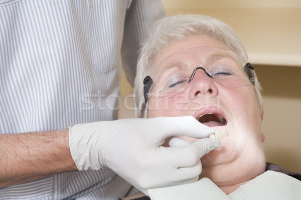 Dentist in exam room fitting dentures on woman in chair Stock photo © monkey_business