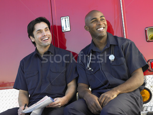 Two paramedics cheerfully doing paperwork, sitting by their ambu Stock photo © monkey_business