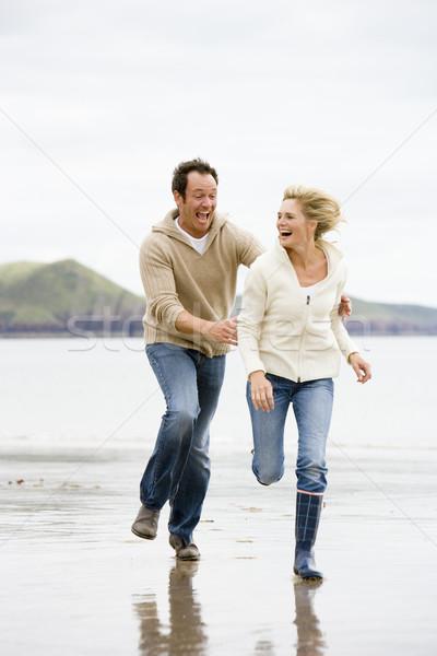 Couple running on beach smiling Stock photo © monkey_business