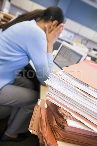 Businesswoman in cubicle with laptop and stacks of files Stock photo © monkey_business