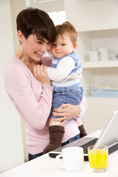 Woman With Baby Working From Home Using Laptop Stock photo © monkey_business