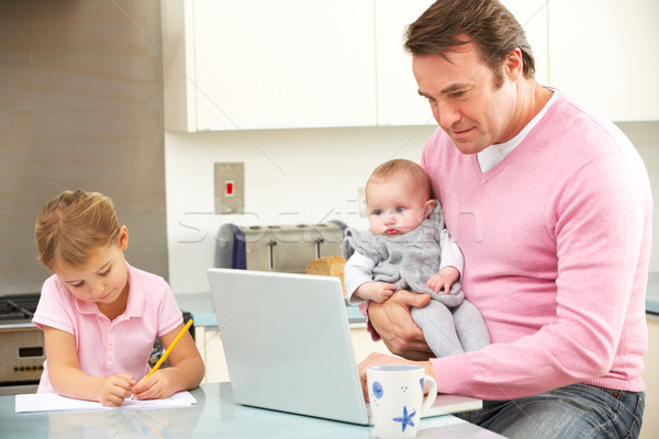 Father with children using laptop in kitchen Stock photo © monkey_business