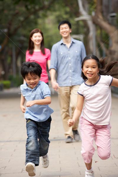 Stock photo: Chinese Family Walking Through Park With Running Children