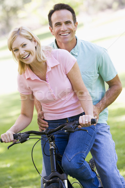 Stock photo: Couple on one bike outdoors smiling