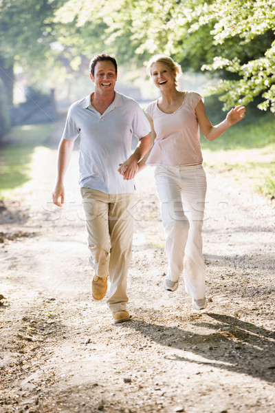 Couple running outdoors holding hands and smiling Stock photo © monkey_business