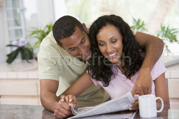 Couple in kitchen with newspaper and coffee smiling Stock photo © monkey_business