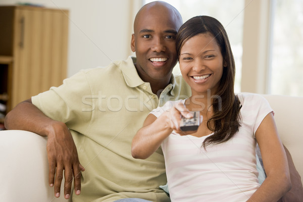 Couple in living room with remote control smiling Stock photo © monkey_business