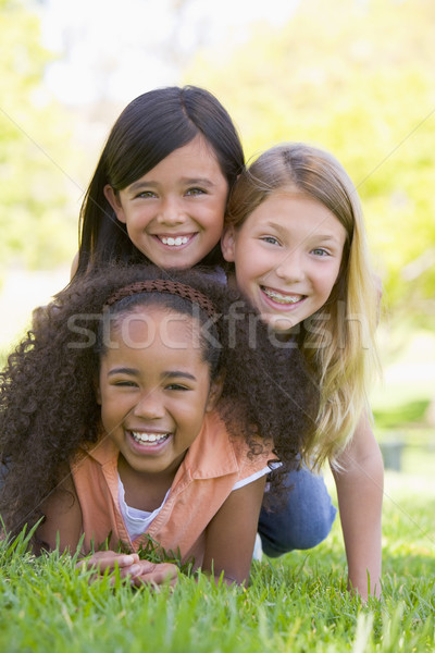 Three young girl friends piled up on top of each other outdoors  Stock photo © monkey_business