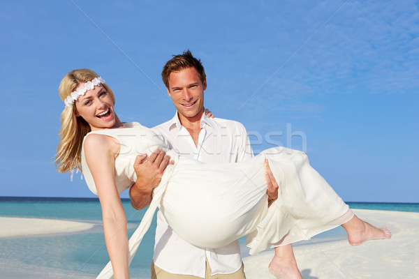Groom Carrying Bride At Beautiful Beach Wedding Stock photo © monkey_business