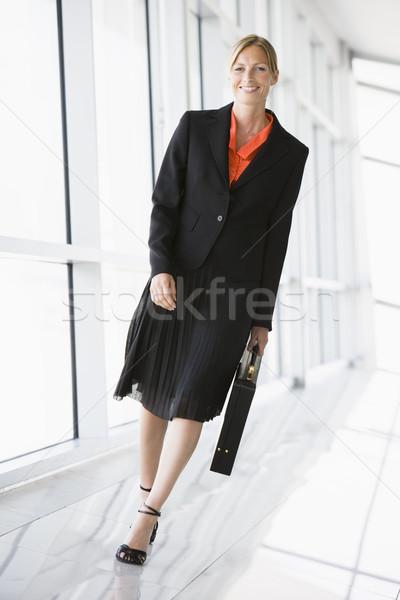 Businesswoman walking in corridor smiling Stock photo © monkey_business