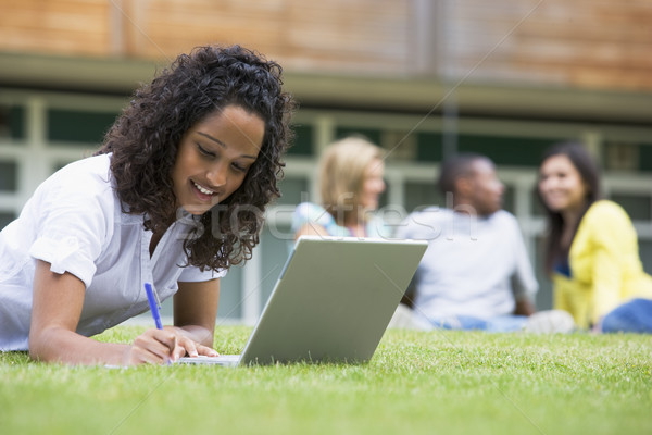 Young woman using laptop on campus lawn, with other students rel Stock photo © monkey_business