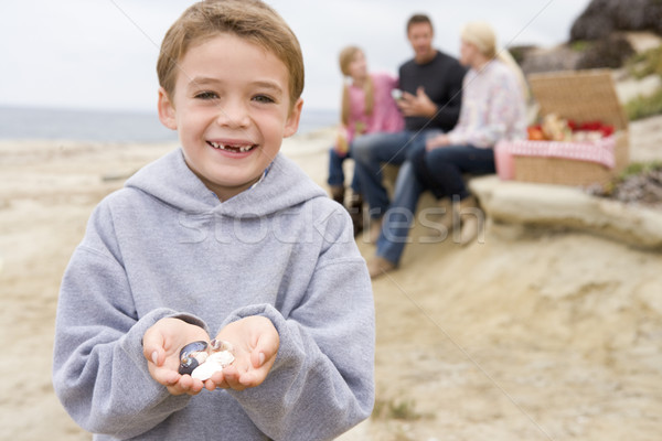 Stock photo: Family at beach with picnic smiling focus on boy with seashells