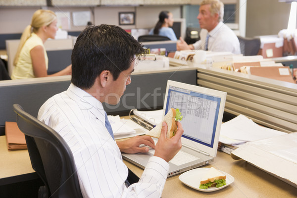 Businessman in cubicle at laptop eating sandwich Stock photo © monkey_business