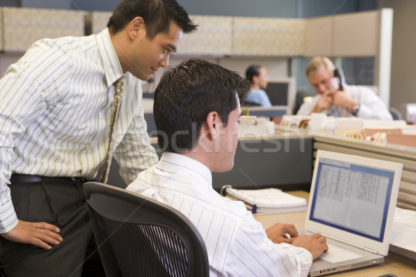 Two businessmen in cubicle looking at laptop Stock photo © monkey_business