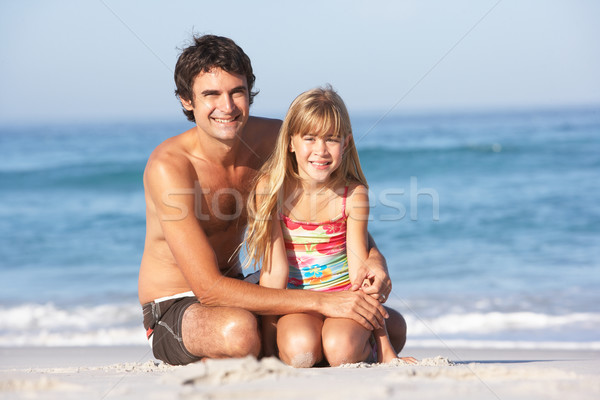 Father And Daughter Wearing Swimwear Sitting On Sandy Beach Stock photo © monkey_business