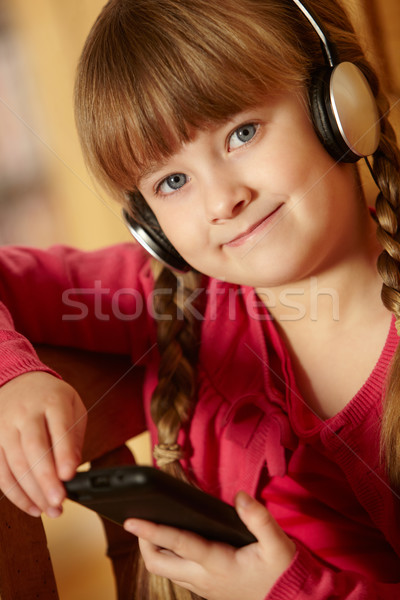 Young Girl Sitting On Wooden Seat Listening To MP3 Player Stock photo © monkey_business