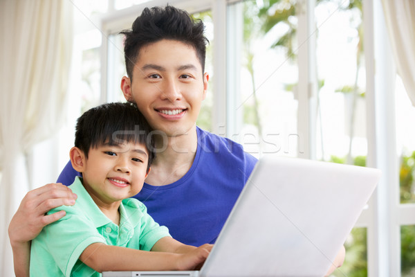 Chinese Father And Son Sitting At Desk Using Laptop At Home Stock photo © monkey_business