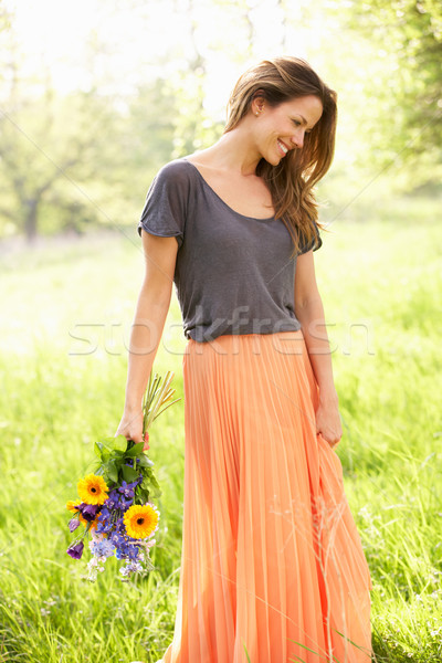 Woman Walking Through Summer Field Carrying Bouquet Of Flowers Stock photo © monkey_business