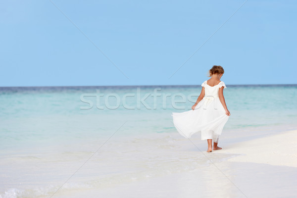 Young Girl In Bridesmaid Dress Walking On Beautiful Beach Stock photo © monkey_business