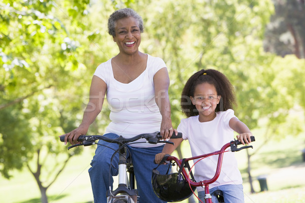 Grandmother and granddaughter on bikes outdoors smiling Stock photo © monkey_business