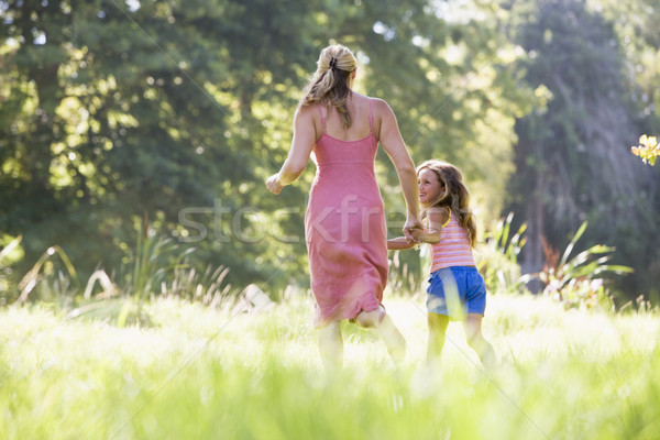 Stock photo: Woman and young girl running outdoors holding hands and smiling