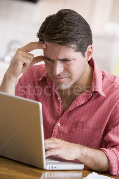 Man in kitchen using laptop frowning Stock photo © monkey_business