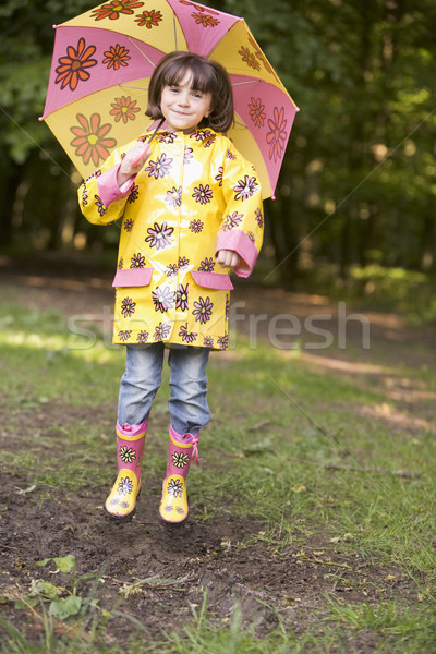 Young girl outdoors with umbrella jumping and smiling Stock photo © monkey_business