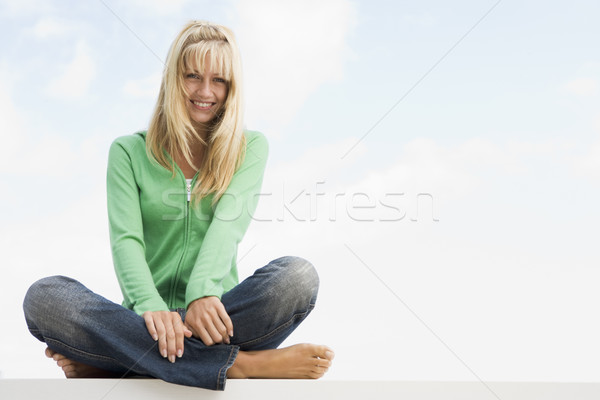 Mujer sesión cruz fuera cielo azul feliz Foto stock © monkey_business