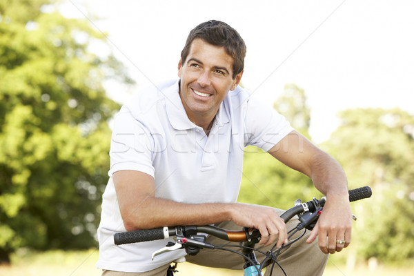 Stock photo: Young man riding bike in countryside