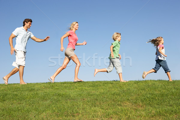 Young family, parents with children,  running through field Stock photo © monkey_business