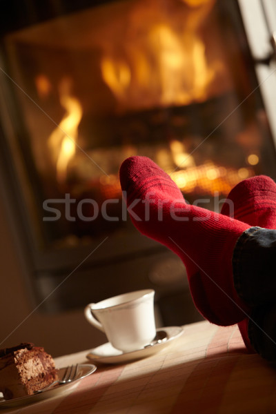 Close Up Of Mans Feet Relaxing By Cosy Log Fire With Tea And Cak Stock photo © monkey_business