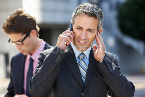 Businessman Speaking On Mobile Phone In Noisy Surroundings Stock photo © monkey_business