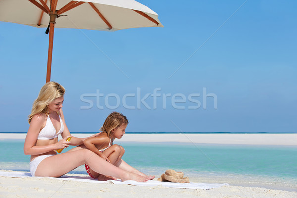 Mother Protecting Daughter With Sun Lotion On Beach Holiday Stock photo © monkey_business