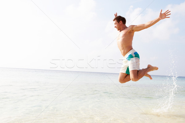 Man Jumping In The Air On Tropical Beach Stock photo © monkey_business
